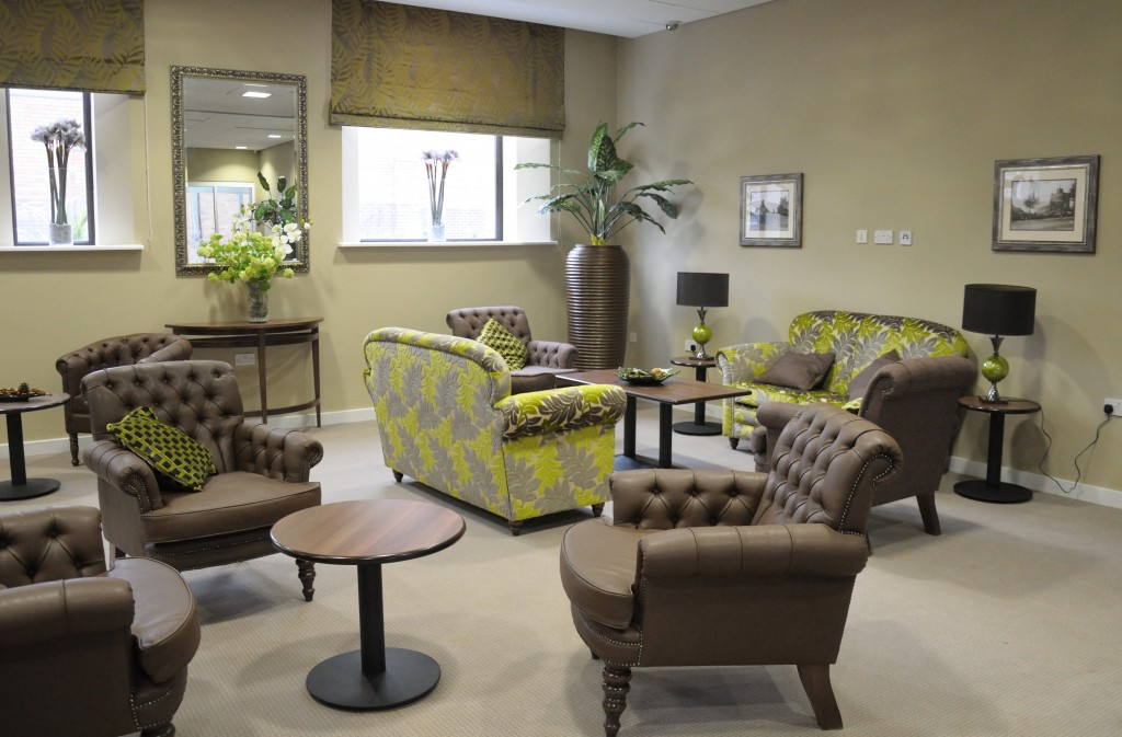 sitting room at Bournville House shows comfortable and modern chairs, sofas and coffee tables in light green and brown.